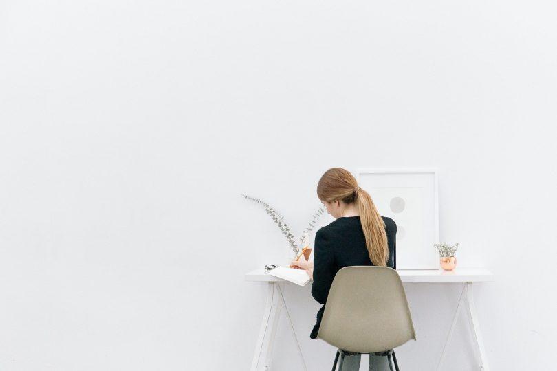 Imagem de uma jovem mulher empreendedora sentada em uma cadeira de frente para uma mesa trabalhando.