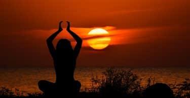 Imagem de uma garota em posição de meditação e ao fundo um lindo por do sol.