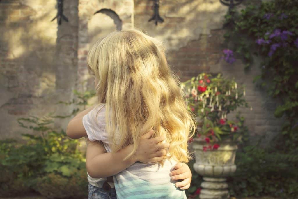 Imagem de duas crianças se abrançado em um lindo jardim.