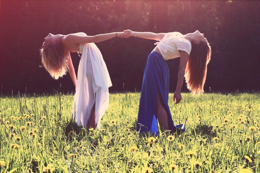 Imagem de duas garotas dando as mãos. Elas estão em um lindo jardim florido. Usam saias longas e estão felizes, praticando a gentileza entre elas.