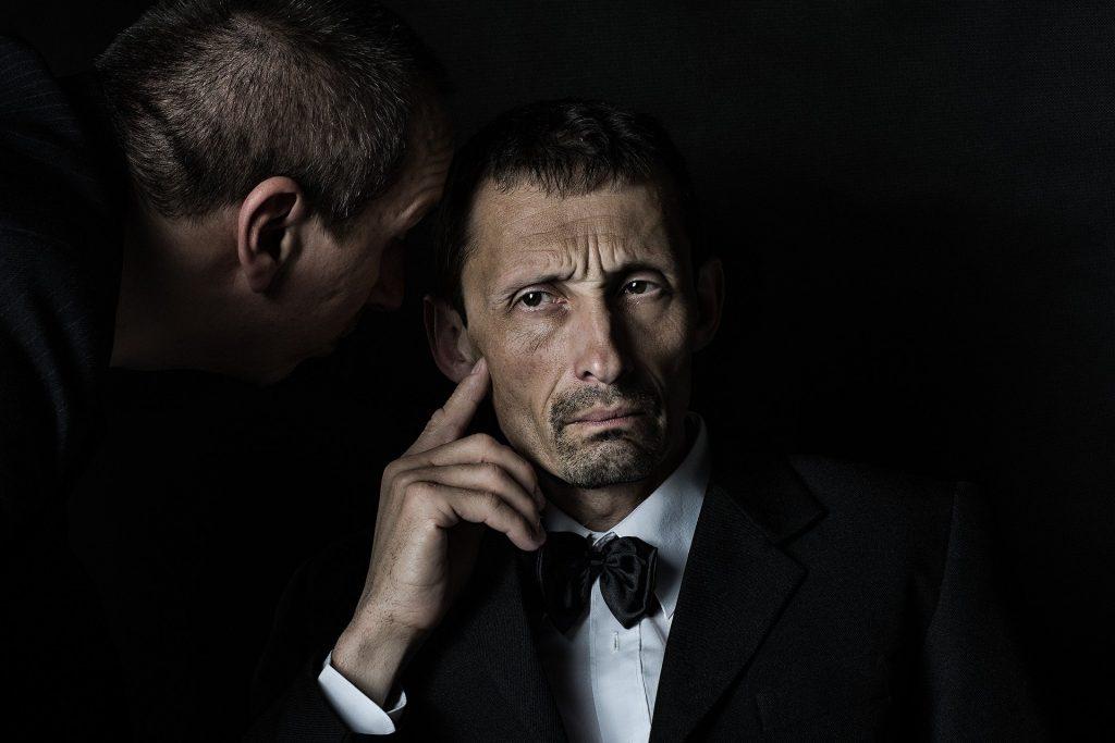 Imagem de dois senhores. Um está sentando e ouvindo o que o outro está dizendo em seu ouvido.