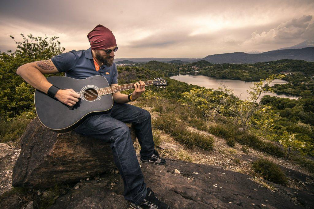 Imagem de um homem tocando um violão. Ele está sentado em uma pedra e ao fundo uma linda montanha com um rio ao centro.