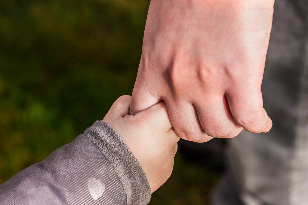 Imagem de uma pessoa adulta de mãos dadas com uma criança.