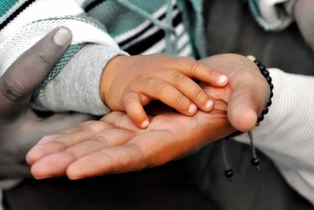 Imagem das mãos de uma pessoa adulta e sobre ela as mãos de uma criança pequena, demonstrando o um gesto de autocuidado de pai com o filho.
