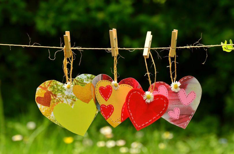 Imagem de quatro corações recortados e feitos em papel colorido, pendurados em um varal por um pregador.