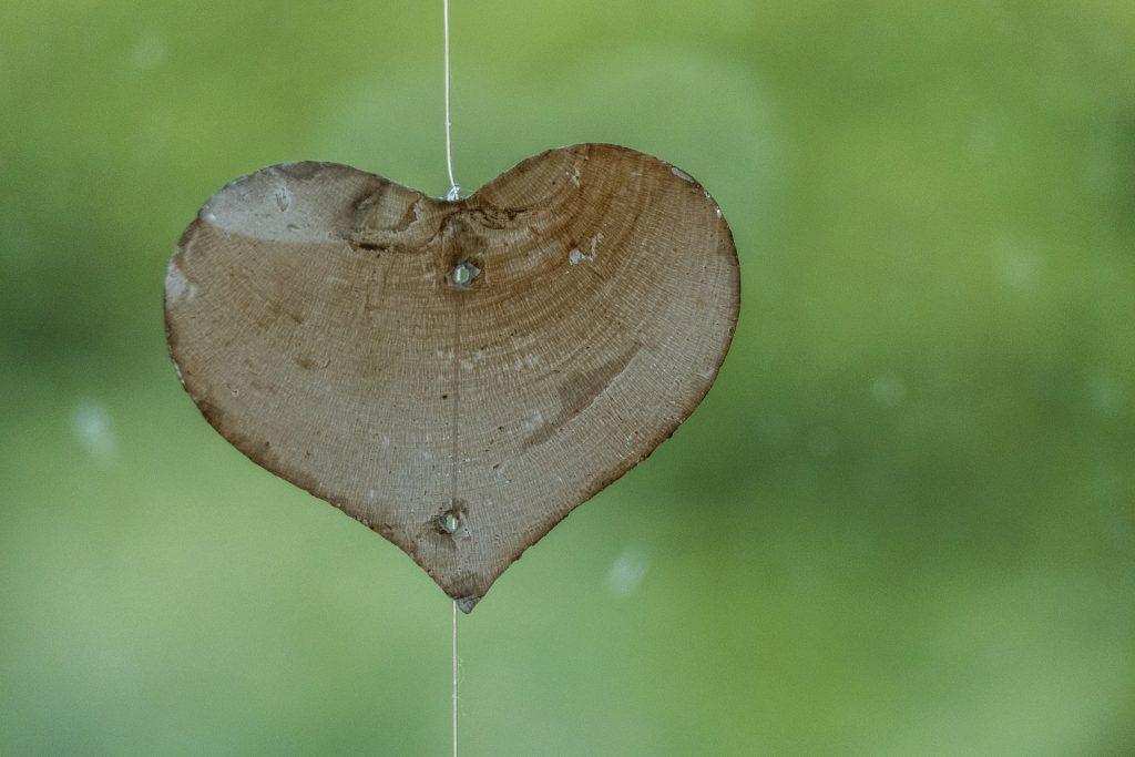 Imagem de um coração talhado em uma madeira leve, suspenso por um fio de nylon, representando o amor próprio.