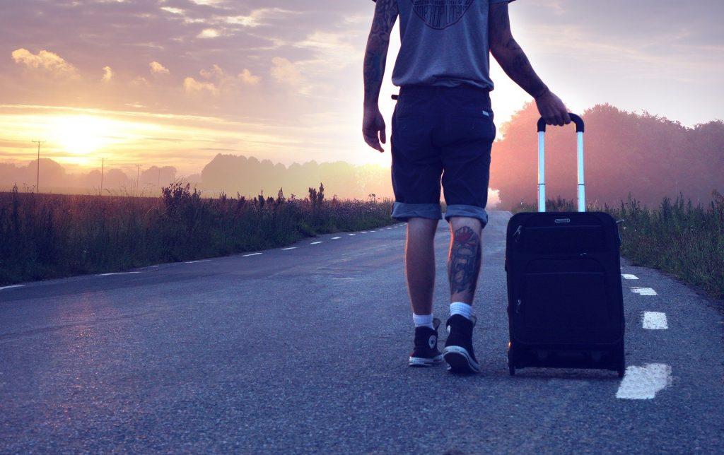Imagem de um homem caminhando em uma estrada asfaltada. Ele usa uma bermuda jeans, tênis all star preto e camiseta cinza. Em uma das mãos traz uma bagagem de viagem.