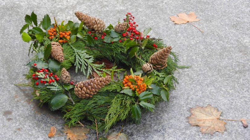 Imagem de uma llinda guirlanda de natal feita na cor verde, decorada com pinhas, flores na cor laranja e vermelho.