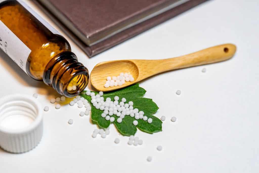 Imagem de remédio homeopático feito para animais. Os remédios estão dentro de um frasco de vidro que está colocado sobre uma mesa branca e ao lado dele uma colher de madeira e uma folhagem da erva medicinal.