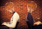 Imagem de dois homens vestidos de social. Eles estão sentados um de costas para o outro e ambos estão mexendo no celular e no computador. A cabeça dos dois é representada por uma lâmpada que configura a ideia, a criatividade.