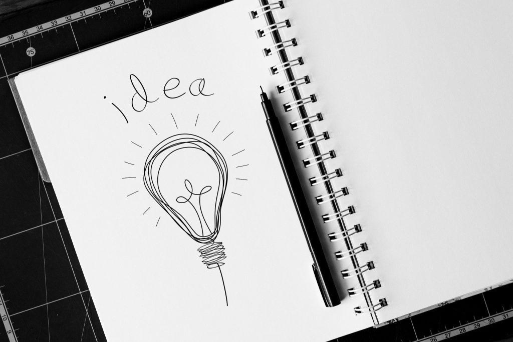 """Imagem em preto e branco de um caderno de desenho grande. Nele está desenhado uma lâmpada e sobre ela está escrito a palavra """"idea"""". Ao lado da lâmpada desenhada uma caneta de desenho na cor preta."""