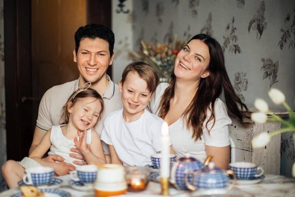Família sentada à mesa. Todos estão sorrindo.
