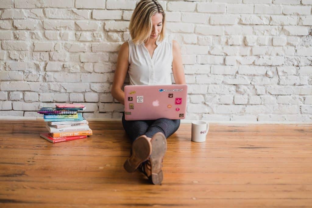 Imagem de uma mulher sentada no chão com piso de madeira ela está segurando um notebook e trabalhado com redes sociais.