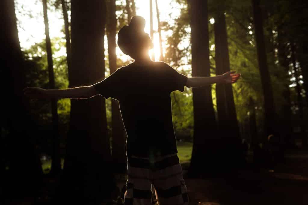 Jovem branco com os braços abertos na floresta.