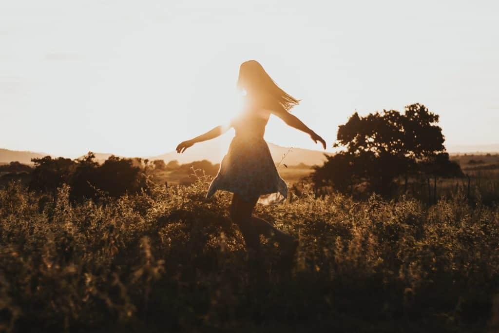 Mulher dançando em um gramado verde com o pôr-do-sol de fundo.