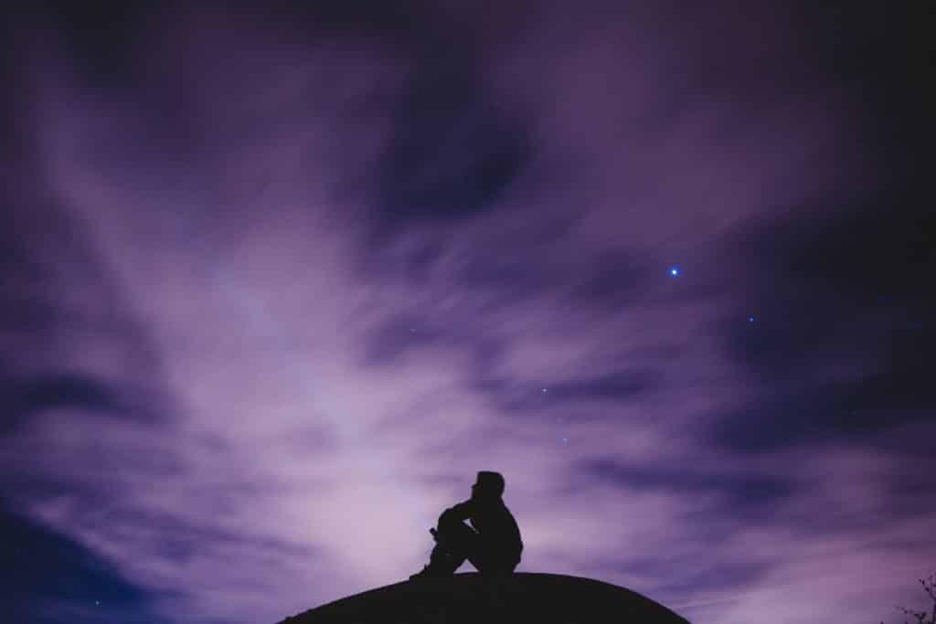 Silhueta de homem sentado com céu roxo ao fundo.
