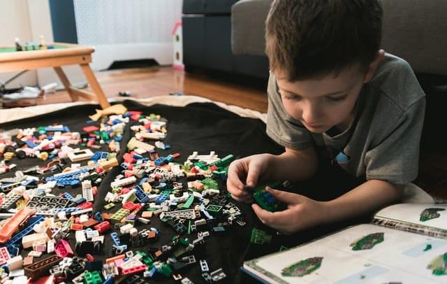 Menino brincando com peças de lego espalhadas no chão
