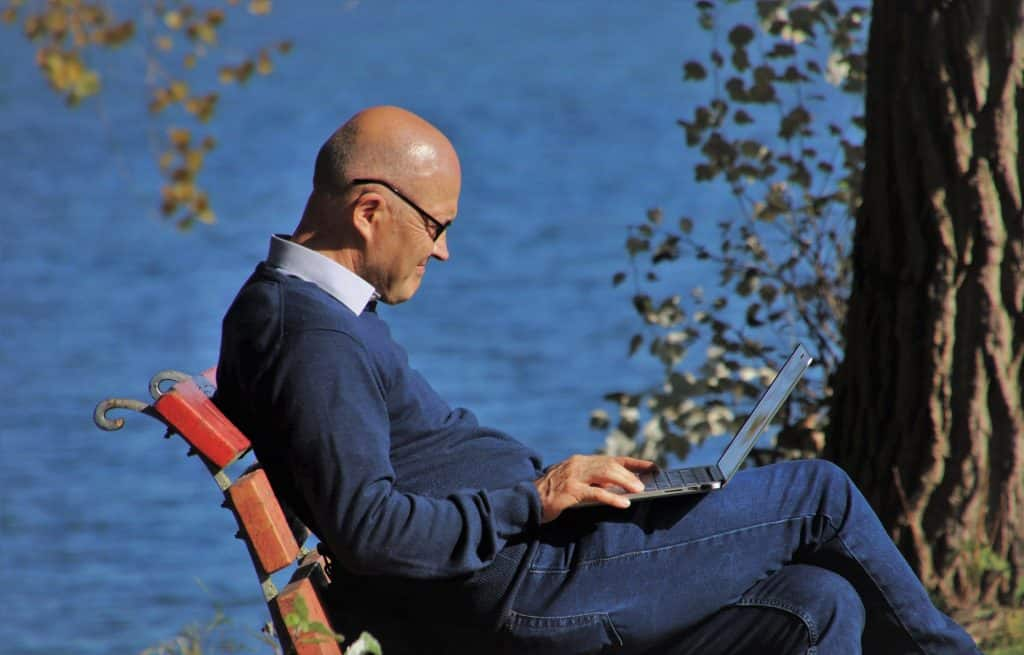 Imagem de um senhor sentado em um banco de mandeira. Ele está mexendo no notebook. Ele usa blusa de frio e calça jeans. Ao fundo a imagem do mar azul.
