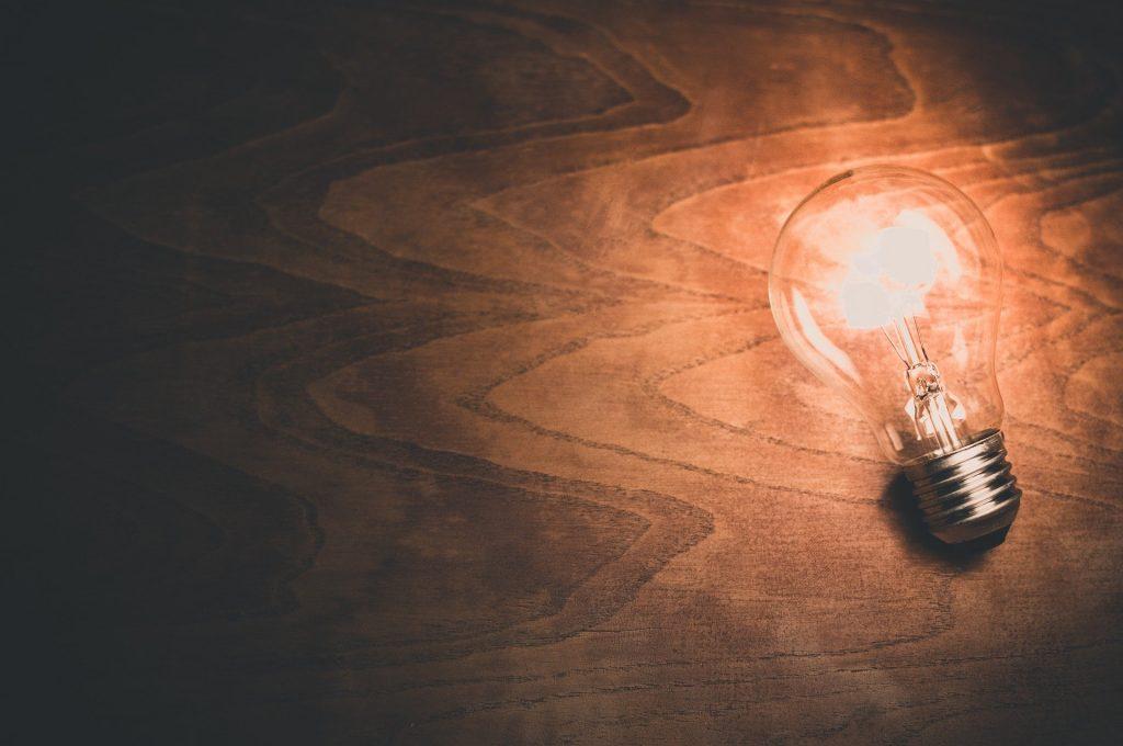Imagem de uma lâmpada acesa sobre uma mesa de madeira escura representando uma ideia, uma criatividade.