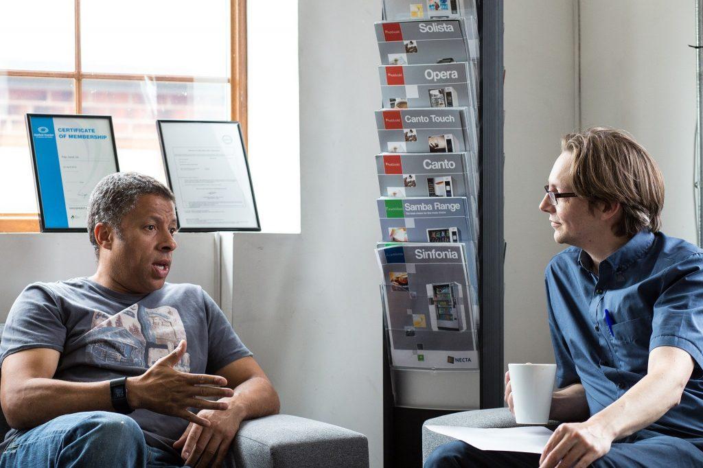 Imagem de uma sala de trabalho e nela dois homens conversando. Um deles segura uma xícara branca de café e o outro apenas gesticula com uma de suas mãos.