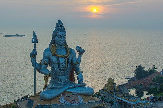 Estátua de Deus Shiva com pôr-do-sol ao fundo.