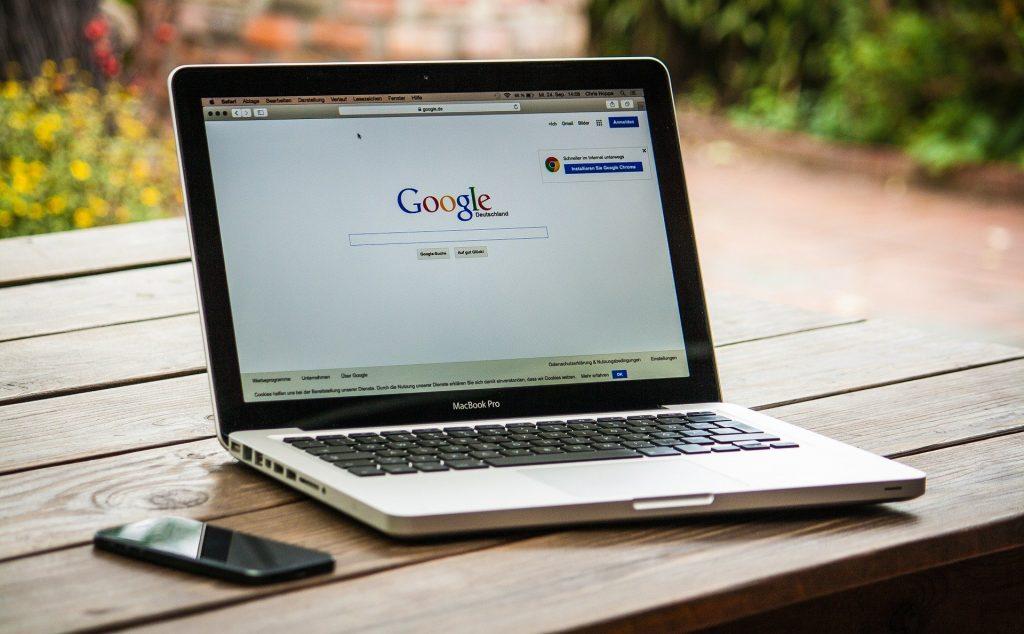 Imagem de um notebook aberto na página do google. O computador está sobre uma mesa de madeira e ao lado dele um aparelho de telefone celular.