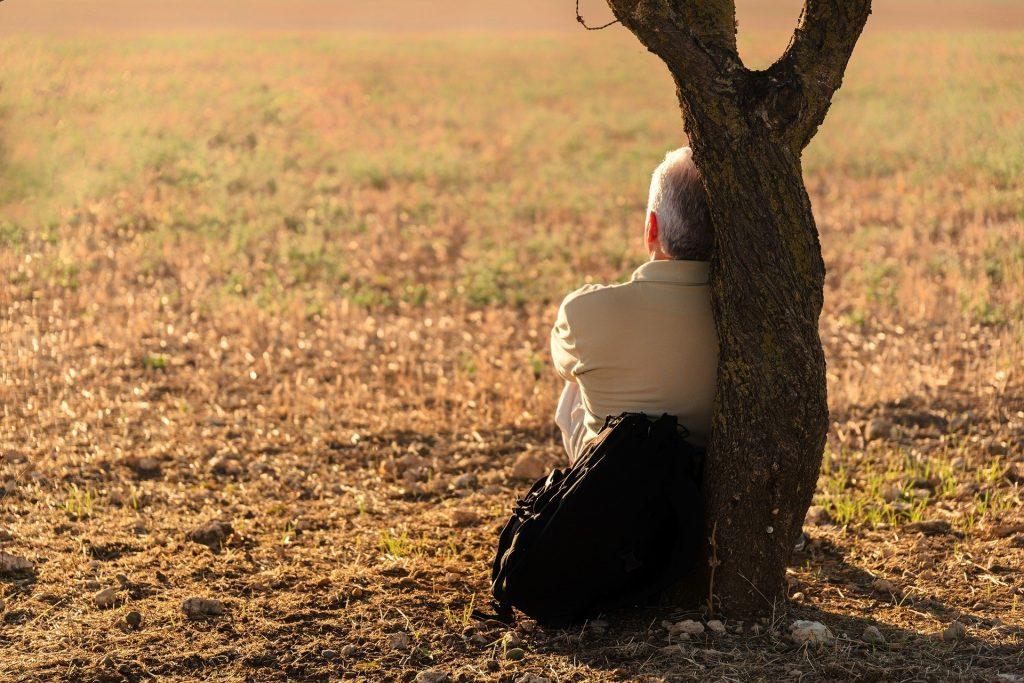 Imagem de um campo gramado e de um homem sentado e encostado em uma árvore. Ele está só e pensativo.