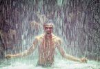 Imagem de um homem negro sorrindo e feliz e ao fundo uma cachoeira.
