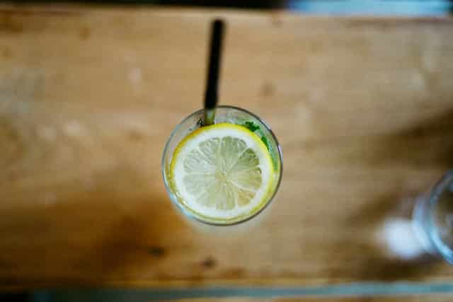 Copo com água e suco de limão com rodela de limão visto de cima
