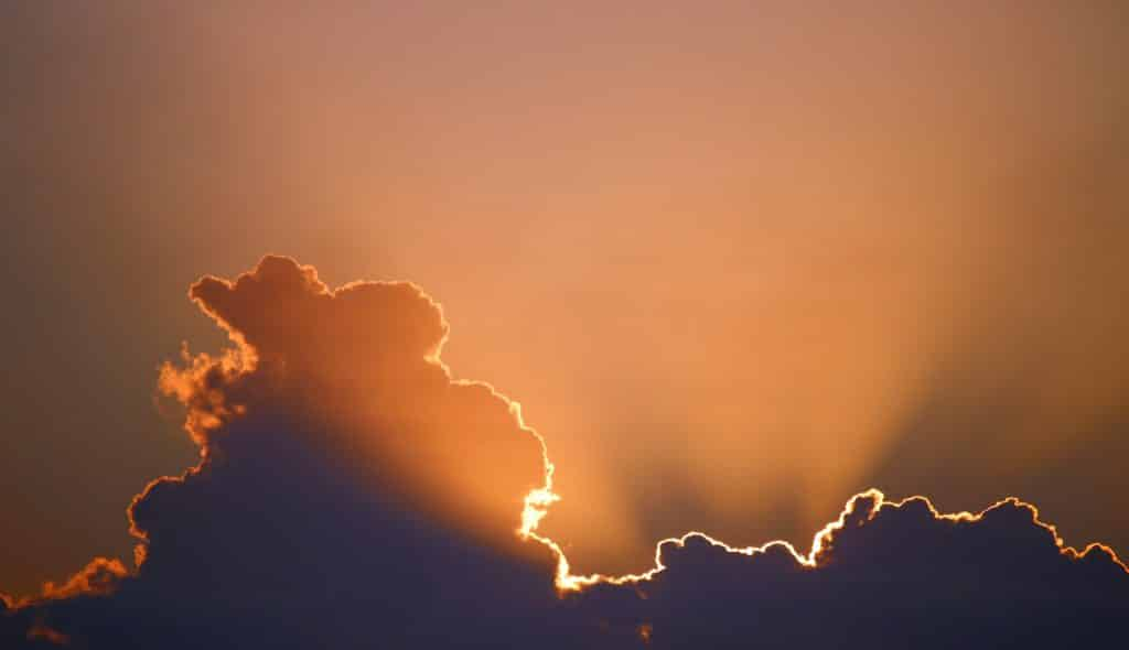 Foto de nuvens com a luz do sol saindo por elas.