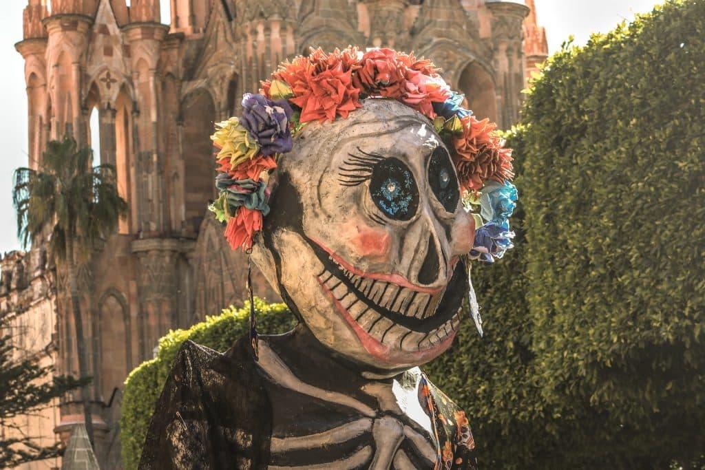Imagem da Deusa da Morte, La Catrina. Ela usa uma máscara de caveira e um arco de flores em sua cabeça. Ela está em um jardim e ao fundo um castelo antigo.