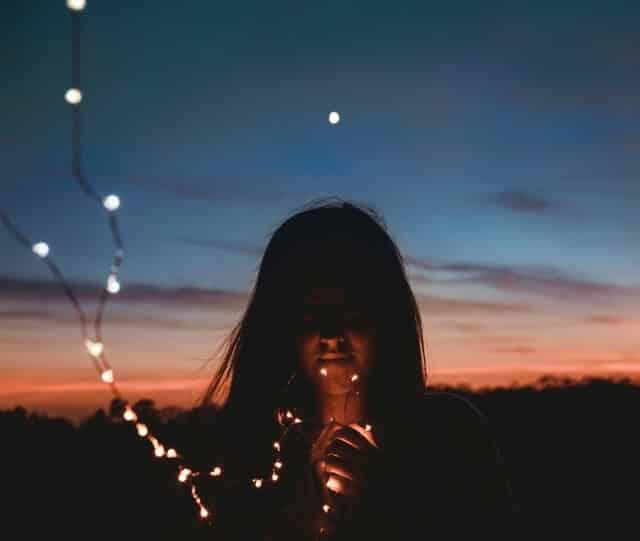 Garota segurando luzes em pisca-pisca com céu escurecendo ao fundo