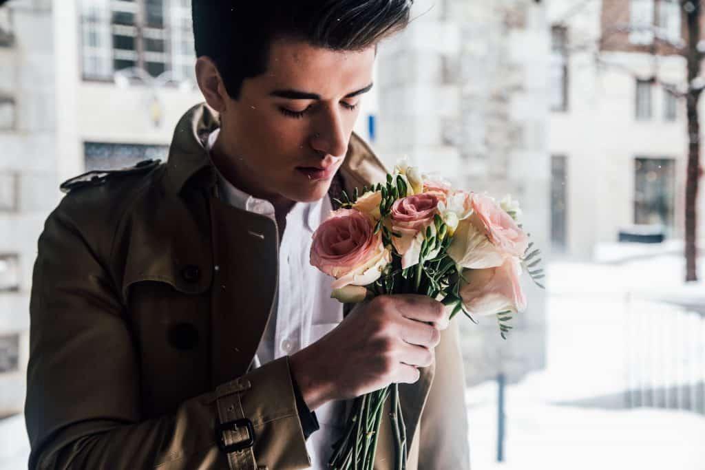 Imagem de um modelo masculino usando uma jaqueta de frio marrom e uma camisa branca. Em uma das mãos ele segura um ramalhete de rosas.
