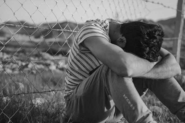 Homem sentado cabisbaixo em grama atrás de grade em foto preta e branca