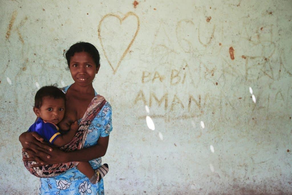 Imagem de uma mulher segurando no colo uma criança. A criança está segurando o seio dela pois acabou de amamentar.