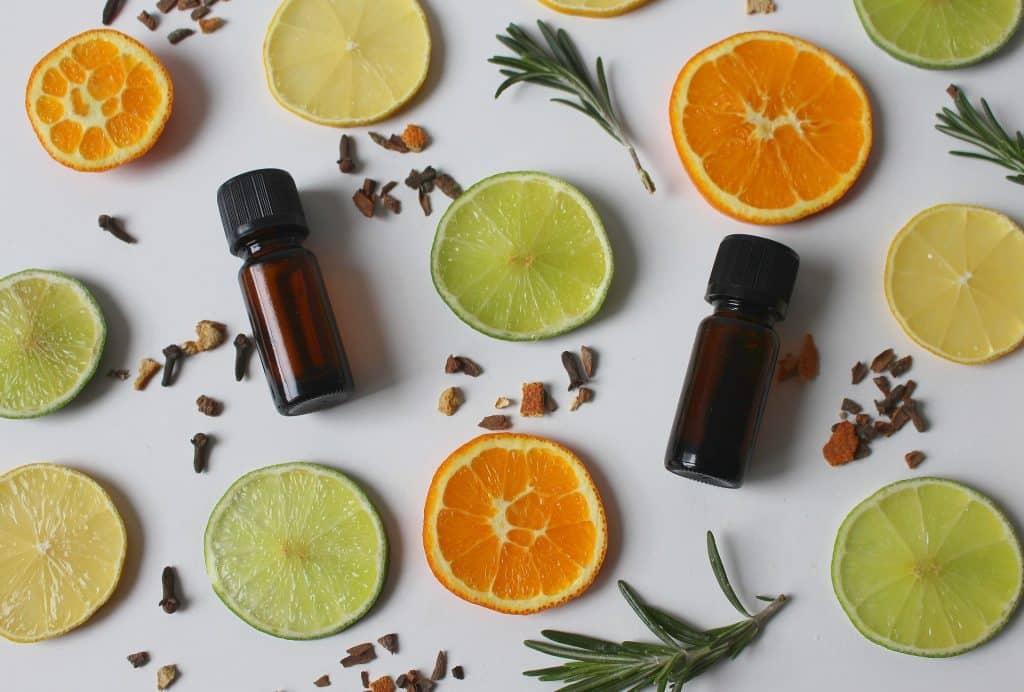 Imagem de vários ingredientes para a elaboração de um óleo essencial de cravo. Temos limões, alecrim e cravos.