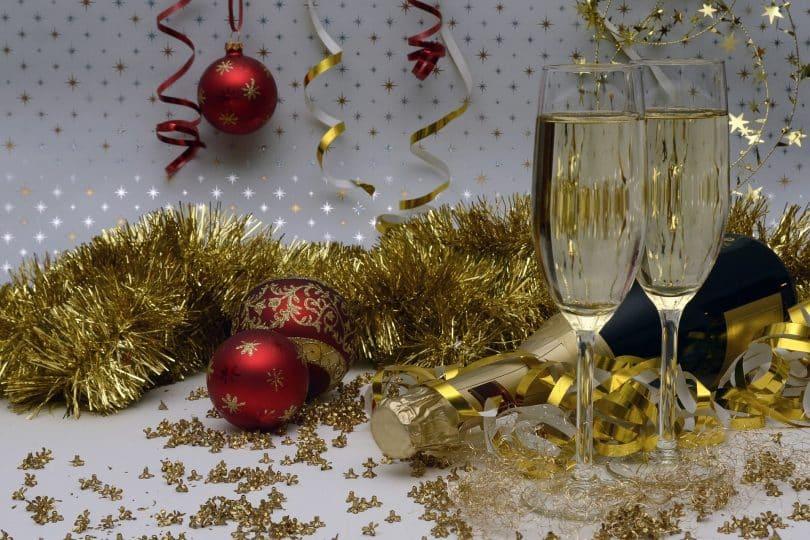 Imagem de uma decoração bem festiva para celebrar as festas de final de ano. A decoração é composta por: festão dourado, bolas vermelhas e douradas, taças com champanhe, serpentina.