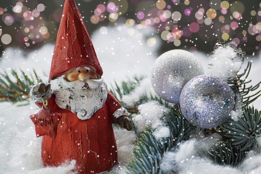 Imagem de um enfeite de Papai Noel pequeno. Ele está disposto sobre um piso forrado com algodão,, representando a neve. Ao lado um ramo da árvores de Natal na cor verde e duas bolas de enfeite na cor prata.