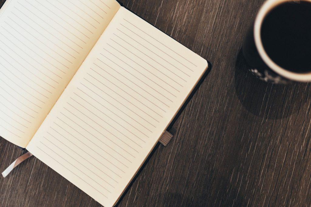 Imagem de um caderno aberto com folhas em branco. Ao lado uma xícara com café. O caderno está sobre uma mesa de madeira.