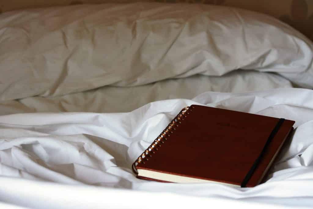 Imagem de uma cama e sobre ela um caderno fechado de anotações. Esse também é um exercício para que a pessoa, depois que ela dormir e sonhar com algo interessante, ela possa acordar e já fazer as suas anotações. Outra forma de exercitar a criatividade.