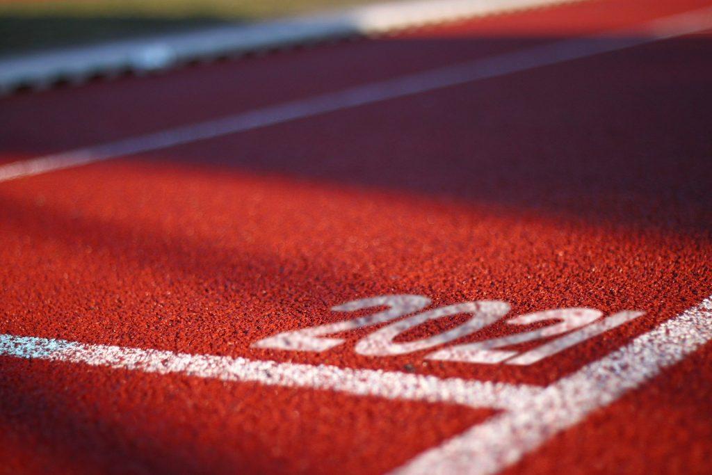 Imagem de uma pista de corrida forrada de vermelho e pintada com faixas brancas nas laterais. Nela está escrito a palavra 2021 em letras grandes na cor branca.