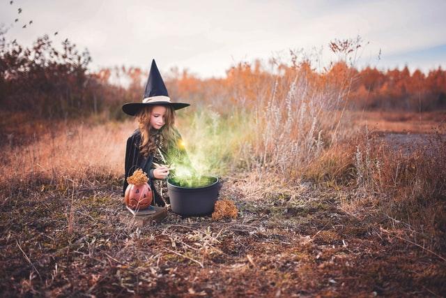 Criança branca vestido de bruxa enquanto brinca com um balde preto.