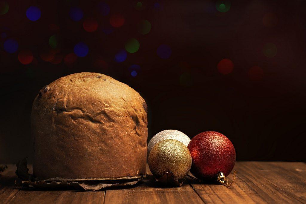 Imagem de um panetone inteiro disposto sobre uma mesa de madeira e ao lado dele três bolas de enfeites de Natal nas cores: vermelho, branco e dourado.