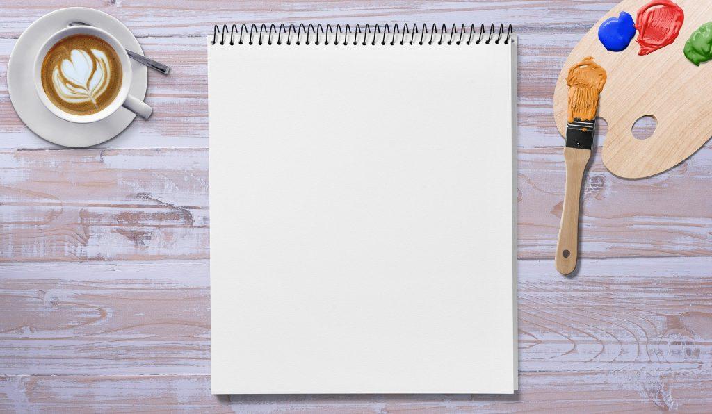 Imagem de um caderno de desenho com folhas em branco. Ao lado uma aquerela com um pincel, e uma xícara branca de porcelana com café.