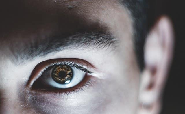 Olho de homem visto de perto iluminado por luz baixa