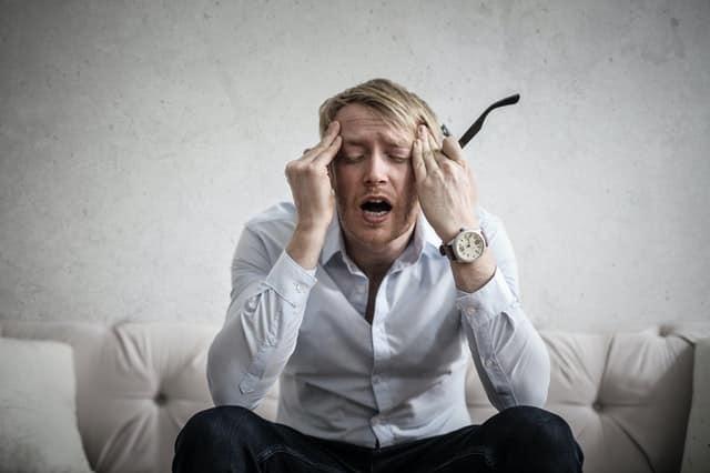 Homem sentado no sofá com mãos na cabeça e expressão de ansiedade