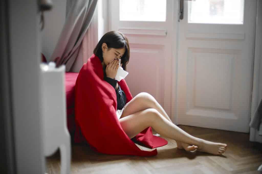 Mulher sentada no chão ensolada em  um edredom com resfriado