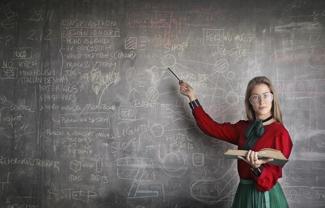 Professora em pé em frente quadro com estudos segurando livro e varinha apontada para quadro