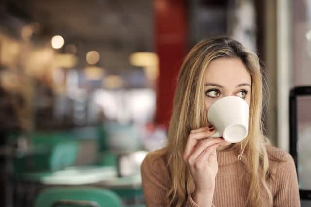 Mulher virando xícara de café na boca