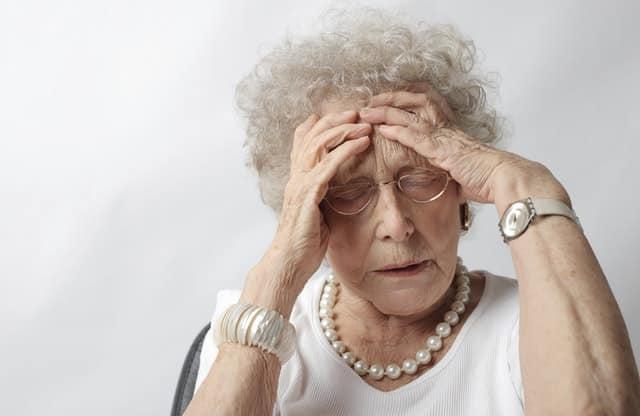 Senhora com mãos na cabeça e expressão de dor